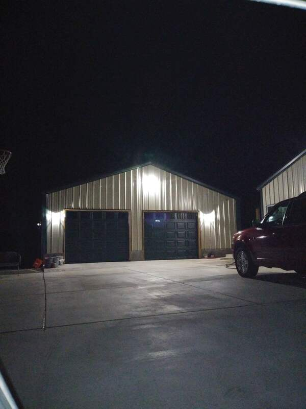 Front of new detached metal building garage at night with lights on.